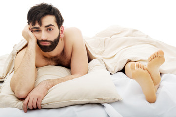 Young depressed man in bed.