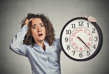stressed corporate employee holding clock looking anxiously runn