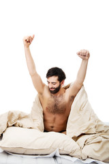 Man waking up in bed and stretching his arms.