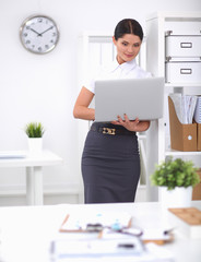 Attractive businesswoman standing in office with laptop