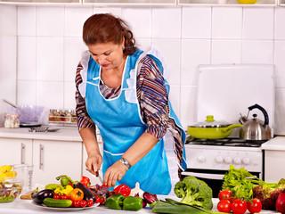 Mature woman preparing at kitchen.