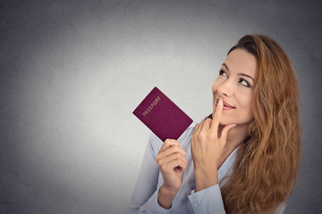 smiling woman holding passport looking up imagining new life