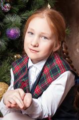 Рыжая девочка в школьной форме у елки в новый год
