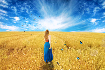 woman in dress standing walking wheat field sunny day blue sky