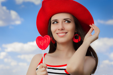 Beautiful Girl with Heart Lollipop and Straw Hat on Blue Sky