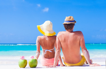 back view of couple sitting on tropical beach with two fresh