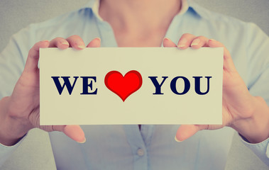 Woman hands holding we love you sign grey background