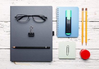 Workplace. White wooden table with notepad, colorful pencils and