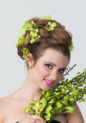 Portrait of woman with orchid flower in hair posing