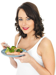 Young Woman Eating Poached Salmon and Vegetables