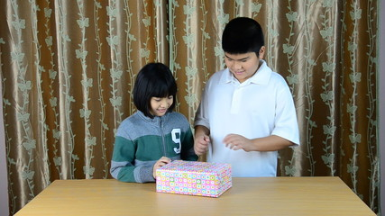 Brother and sister was opening gift of parent. HD