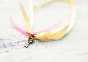 Ornate old little key on ribbon lying on wooden table