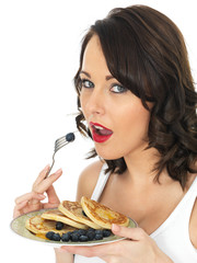 Young Woman Eating Pancakes with Blueberries