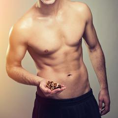 Shirtless muscular man holding various nuts