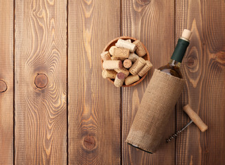 White wine bottle, bowl with corks and corkscrew. View from abov