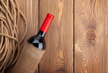 Red wine bottle over rustic wooden table background. View from a
