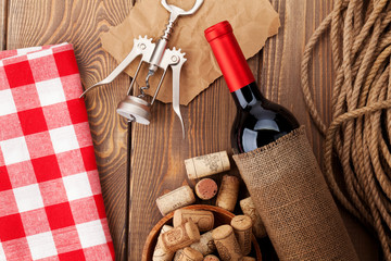 Red wine bottle, bowl with corks and corkscrew. View from above