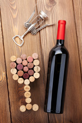 Red wine bottle, glass shaped corks and corkscrew. View from abo