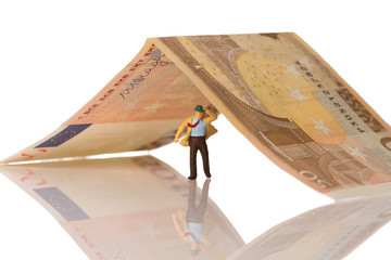 businessman figurine running on a euro banknote on white