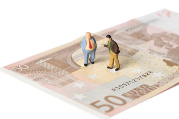 businessmen standing on euro banknotes