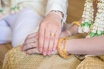 Thai groom wearing wedding ring for his bride
