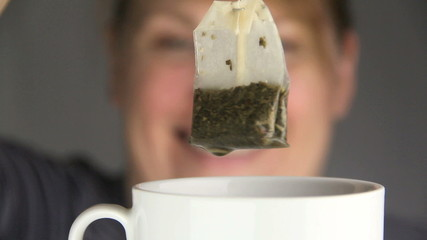 Woman dipping a teabag slowly into a cup of tea.