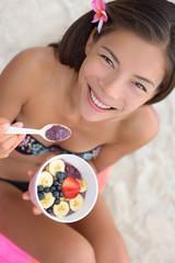 Acai bowl - woman eating healthy food on beach