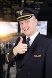 joyful young pilot with thumb up in cockpit
