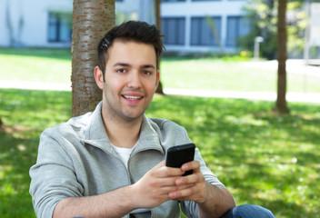 Junger Mann im Park schreibt SMS