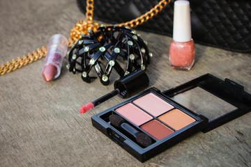 Women's accessories: eyeshadow, nail polish, clip hair, handbag