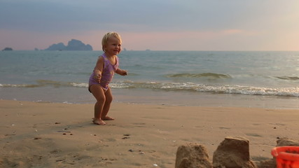 blonde baby girl in purple swimsuit start dance and smile on the