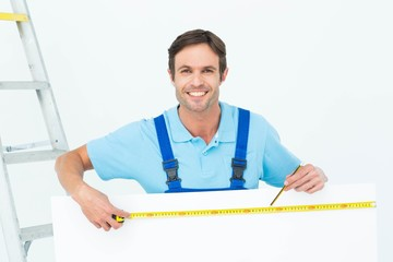 Happy carpenter measuring blank bill board