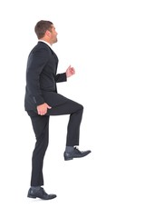 Businessman walking with his leg up