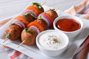 Delicious meatballs on skewers with sauce on a plate horizontal