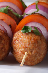 Fried meatballs on skewers with vegetables macro. Vertical