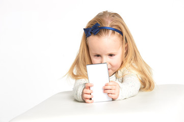 Cute little girl smiling and uses a smartphone, phone.