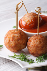 Grilled meatballs nd tomato sauce on a plate  vertical macro