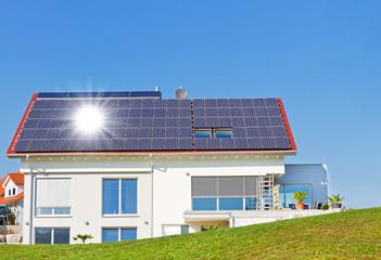 Haus mit Solarzellen und Sonne