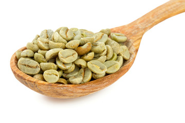 green coffee beans in a wooden spoon