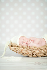 Picture of a newborn baby curled up sleeping in a basket