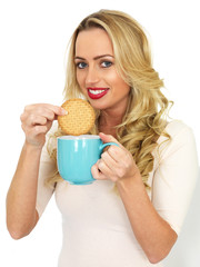 Young Woman Dunking a Biscuit in a Mug of Tea
