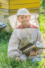 Young beekeeper with painted wooden beehives