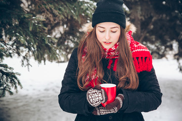 Girl drinking hot tea in the winter forest