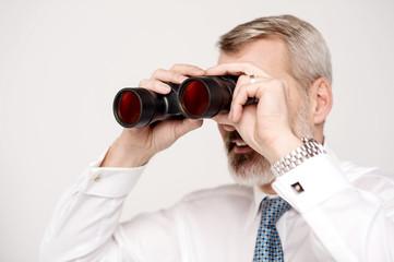 Male execuitve peers through binoculars
