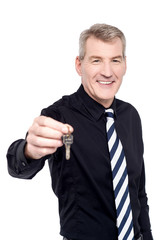 Male realtor showing the keys to camera
