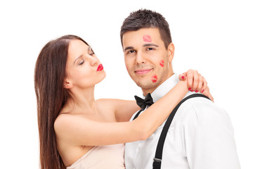 Girl covering a young man in kisses