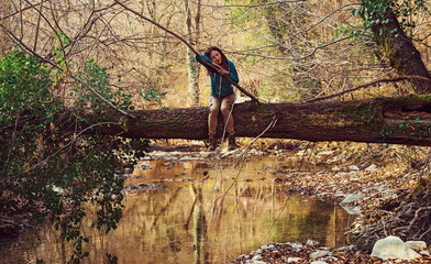 Woman sitting on tree trunk over the river