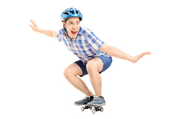 Joyful guy riding a small skateboard