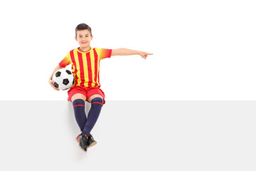 Junior football player pointing with his hand