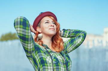 Happy hipster redhead girl in checkered shirt